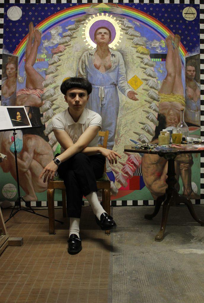 Silvia Flechoso sentada en su estudio con su obra Pandemia de fondo